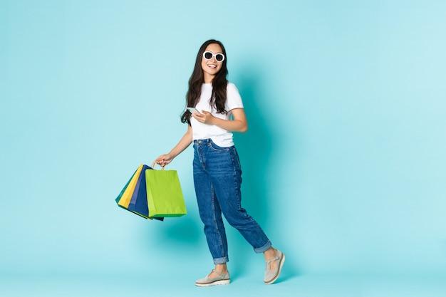 Conceito de moda, beleza e estilo de vida. mulher asiática atraente e sonhadora, caminhando ao longo da parede azul claro com sacolas de compras e smartphone, usando óculos escuros