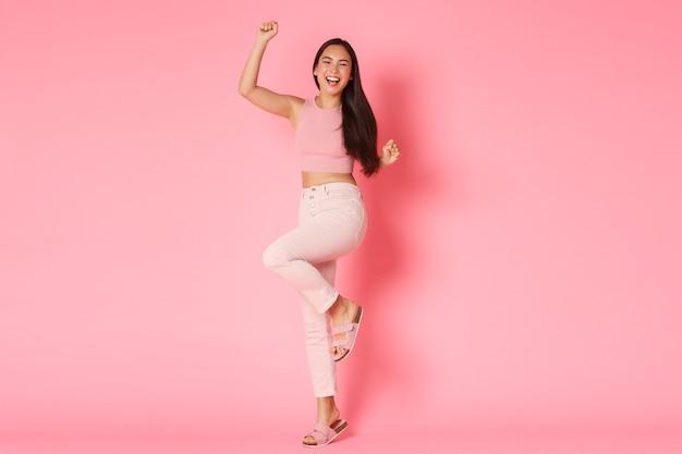 Conceito de moda, beleza e estilo de vida. mulher asiática bem-sucedida e vencedora em roupas elegantes
