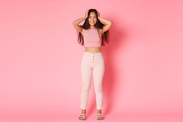Conceito de moda, beleza e estilo de vida. retrato de corpo inteiro de uma garota asiática atraente em roupa de glamour