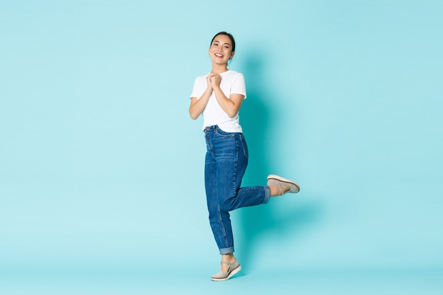 Conceito de moda, beleza e estilo de vida. romântica e sonhadora linda garota asiática em roupa casual linda, junte as mãos posando sobre uma parede azul clara.