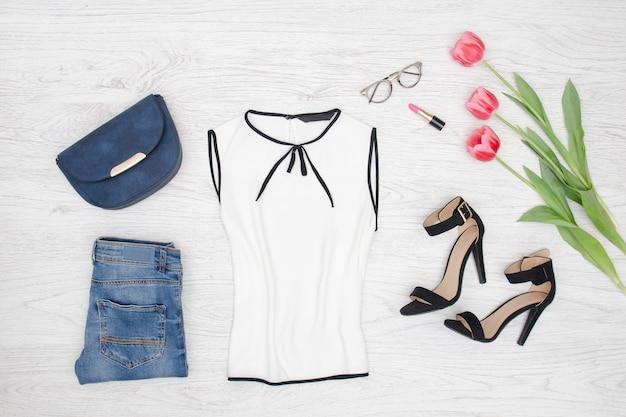 Conceito de moda. blusa branca, óculos, jeans, bolsa e tulipas cor de rosa. vista do topo