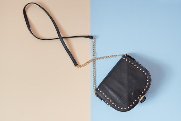 Conceito de moda. bolsa preta. concurso fundo bege e azul.