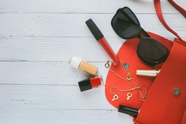 Conceito de moda. bolsa vermelha, produtos cosméticos, óculos de sol, brincos.
