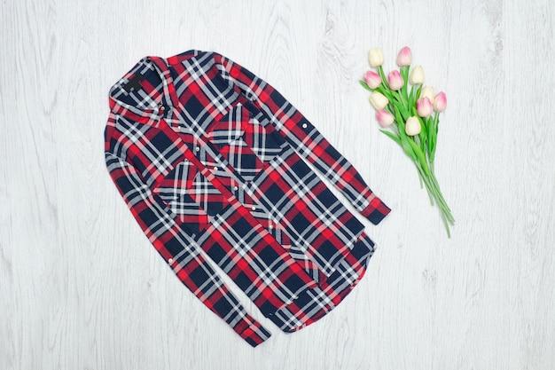 Conceito de moda. camisa quadriculada vermelha e tulipas cor de rosa. fundo madeira