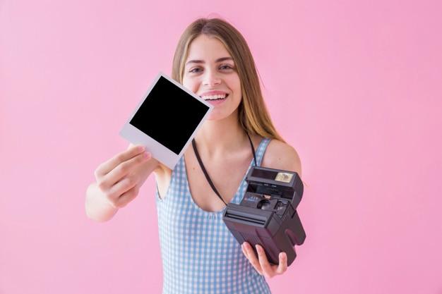 Conceito de moda de verão com mulher mostrando polaroid