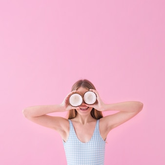 Conceito de moda de verão com mulher segurando coco na frente dos olhos