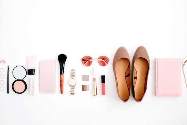 Conceito de moda do blog de beleza. telefone celular de acessórios de estilo rosa feminino, relógios, óculos de sol, caderno, cosméticos, sapatos em fundo branco. camada plana, vista superior