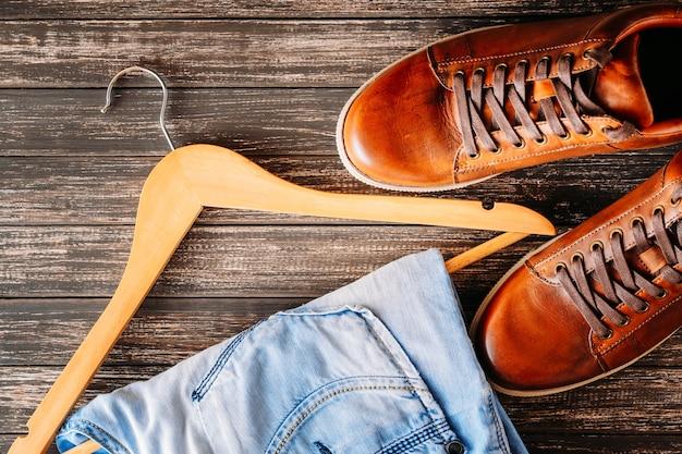 Conceito de moda do homem. sapatos masculinos de couro casual marrom, jeans e cabide em um fundo escuro