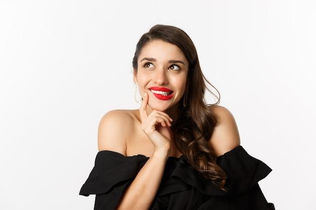 Conceito de moda e beleza. close de uma linda mulher sonhadora com lábios vermelhos, olhando para o canto superior esquerdo e sorrindo, tentada, tendo uma ideia, em pé sobre um fundo branco