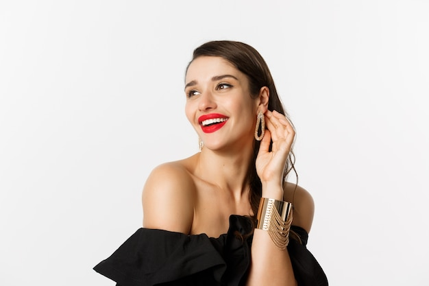 Conceito de moda e beleza. close-up de mulher morena elegante com lábios vermelhos, vestido preto, rindo coquete e olhando para longe, em pé sobre fundo branco.