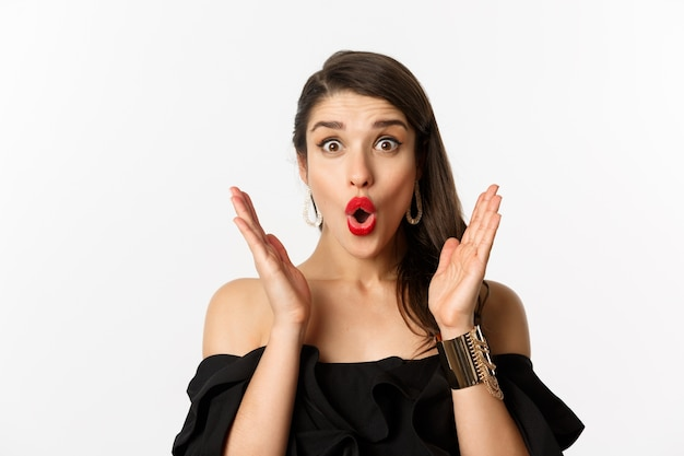 Conceito de moda e beleza. close-up de uma mulher animada com maquiagem e batom vermelho, parecendo surpreso e feliz, em pé sobre um fundo branco.