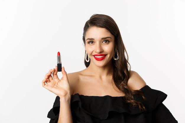 Conceito de moda e beleza. linda mulher vestida de preto aplicando batom vermelho e maquiagem, indo para a festa, em pé sobre um fundo branco