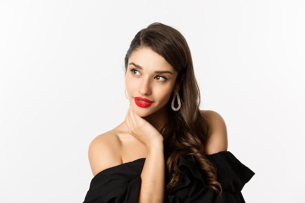 Conceito de moda e beleza. mulher elegante com brincos e vestido preto, parecendo sensual à esquerda, em pé sobre um fundo branco