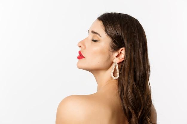 Conceito de moda e beleza. perfil de mulher bonita em pé nua com maquiagem e brincos, parecendo terna e sensual, em pé sobre um fundo branco.