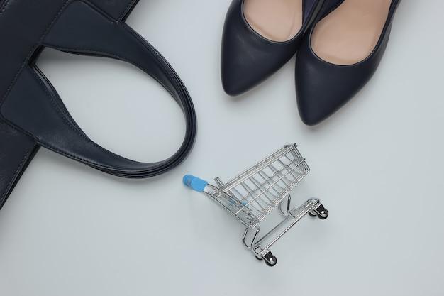 Conceito de moda e compras minimalista. bolsa de carrinho de compras de couro com sapatos de salto alto em fundo branco