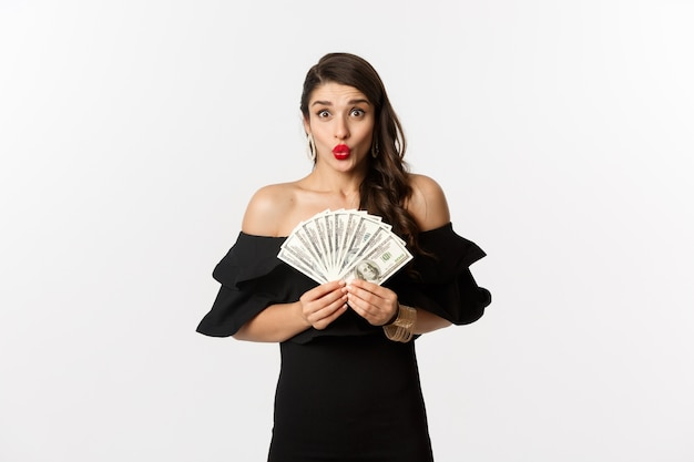 Conceito de moda e compras. mulher animada de vestido preto, com lábios vermelhos, mostrando dinheiro em dólares e olhando espantada com a câmera, fundo branco.