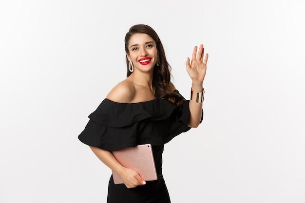 Conceito de moda e compras. mulher jovem elegante com maquiagem glamour, usando um vestido preto, segurando o tablet digital e dizendo oi, acenando com a mão para cumprimentá-lo, fundo branco.