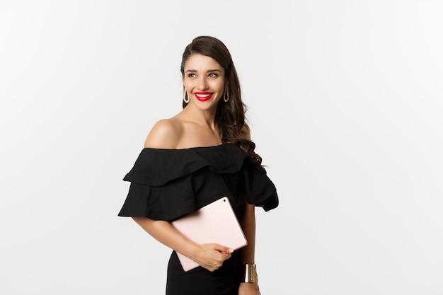 Conceito de moda e compras. mulher jovem elegante com maquiagem glamour, vestido preto, segurando o tablet digital e sorrindo, fundo branco.