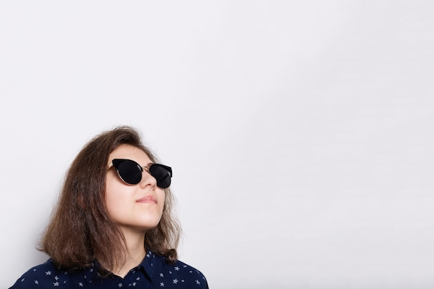 Conceito de moda e estilo. óculos de sol vestindo de uma morena nova elegante elegante que olham isolados acima no branco. jovem modelo de óculos