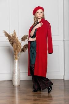Conceito de moda e glamour - mulher elegante em uma boina e um casaco sobre um fundo claro. casaco, boina, roupas, estilo, moda, beleza, mulher jovem
