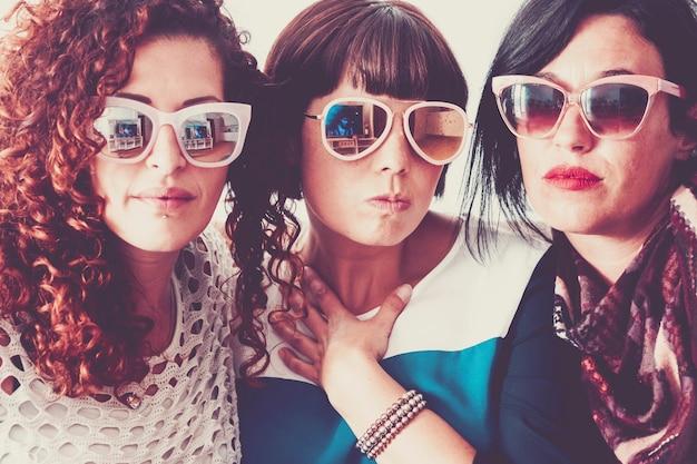 Conceito de moda e moderno com três belas jovens usando óculos escuros juntos em filtro de cores vintage