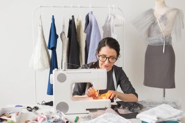 Conceito de moda e pessoas - jovem costureira costura roupas em máquina de costura