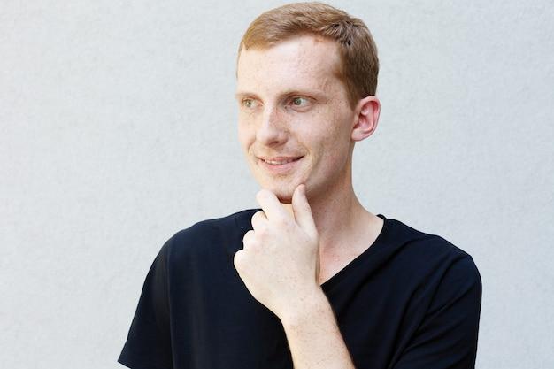 Conceito de moda, estilo, emoções e pessoas - feche o retrato de uma ruiva de um cara lindo e viril com sardas em uma camiseta preta de fundo cinza. segurando seu queixo e pensativamente