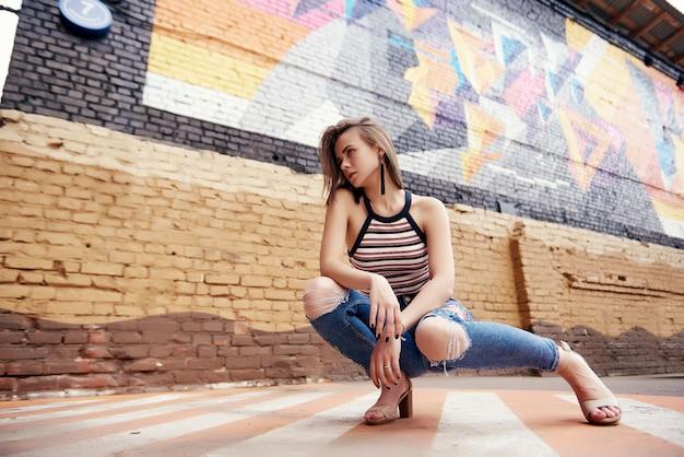 Conceito de moda feminina. cintura ao ar livre acima do retrato da mulher bonita nova que levanta na rua velha.