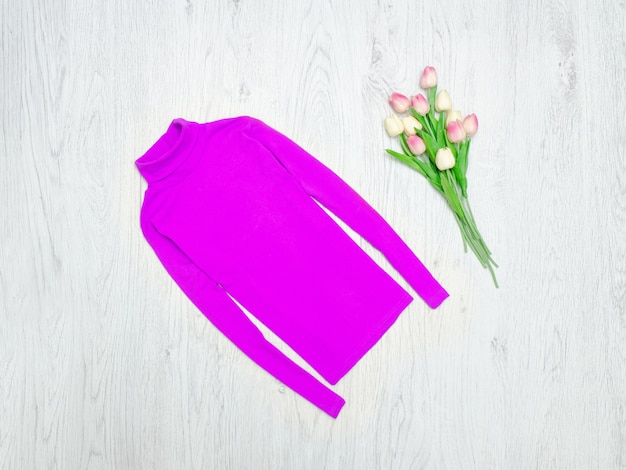 Conceito de moda. gola alta violeta e tulipas cor de rosa. fundo de madeira