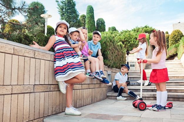 Conceito de moda infantil. grupo de meninos e meninas adolescentes posando no parque