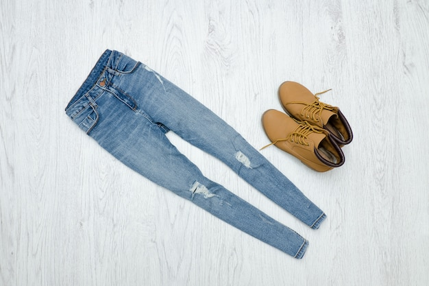 Conceito de moda. jeans e botas rasgados azuis. fundo madeira