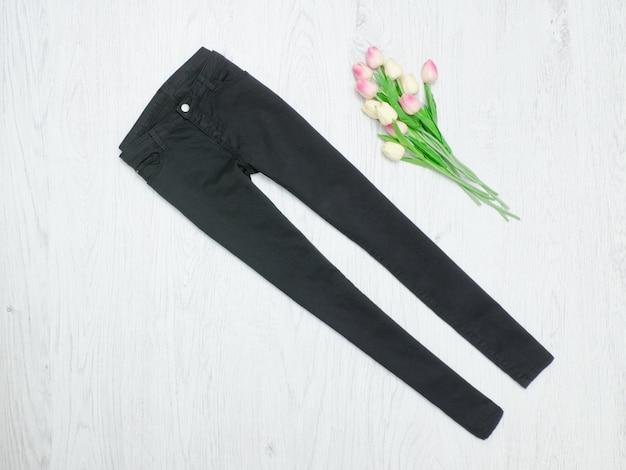 Conceito de moda. jeans preto e tulipas cor de rosa. fundo madeira