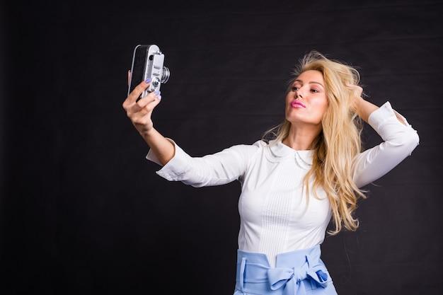Conceito de moda, lazer e beleza - linda modelo loira em uma camisa branca tirando uma selfie no escuro