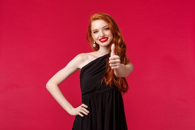 Conceito de moda, luxo e beleza. retrato de mulher ruiva jovem assegurada e satisfeito em elegante vestido preto, mostrar polegar para cima em aprovação ou como sinal, concordar ou garantir boa qualidade