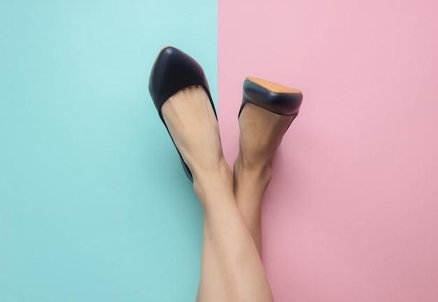 Conceito de moda minimalista pernas femininas com sapatos de couro com saltos em fundo rosa azul pastel