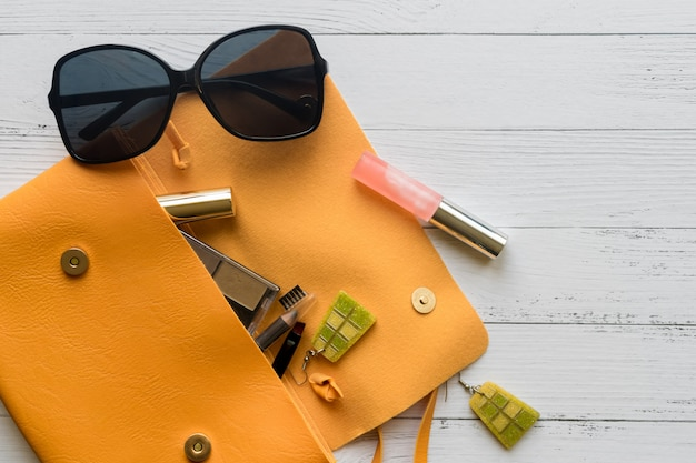 Conceito de moda. produtos cosméticos femininos, óculos de sol, brincos e bolsa laranja.