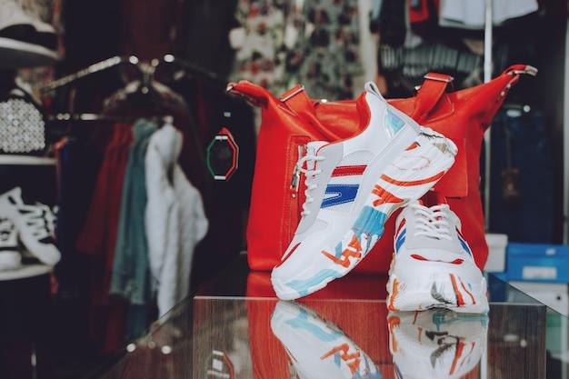 Conceito de moda rápida. bolsa vermelha e sapatos na prateleira na loja, loja.