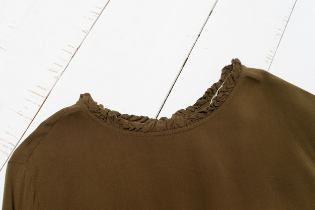 Conceito de moda roupas. gola de blusa cáqui em fundo branco de madeira. vista do topo