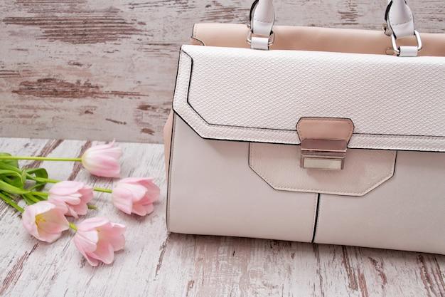 Conceito de moda. saco de luz e tulipas cor de rosa em uma luz de madeira