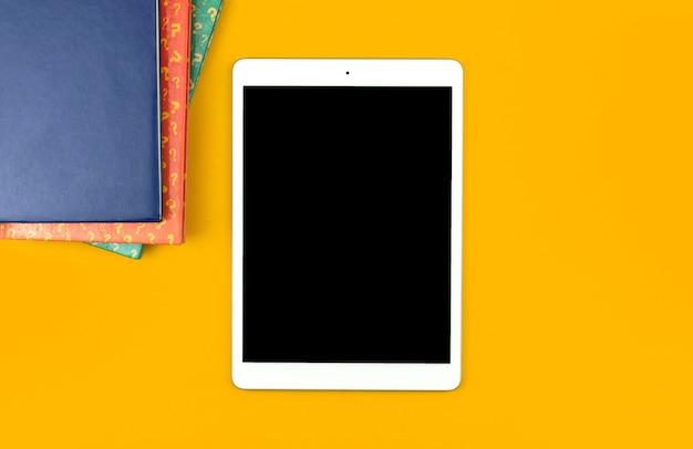 Conceito de modelo de resposta e pergunta de teste, tela de maquete de tablet digital no fundo amarelo da área de trabalho, vista superior e foto do espaço de cópia