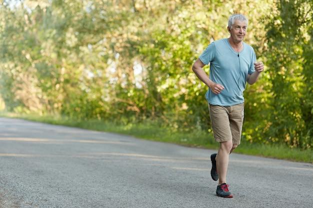 Conceito de motivação de pessoas, aposentadoria e esporte. o ajuste saudável pensionista masculino de cabelos grisalhos é executado no asfalto, ouve a melodia favorita em fones de ouvido, aproveita o tempo de lazer ao ar livre na área rural. corredor de homem