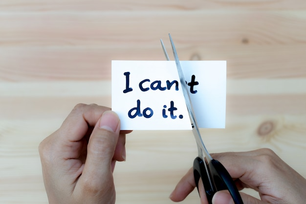 Conceito de motivação, mãos de mulher segurando o cartão eu posso fazê-lo com tesoura.