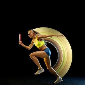 Conceito de movimento e ação no esporte. jovem mulher caucasiana, corredor profissional em fundo preto, líder. corrida de revezamento. esporte, estilo de vida saudável, movimento, bem-estar. desenho abstrato.
