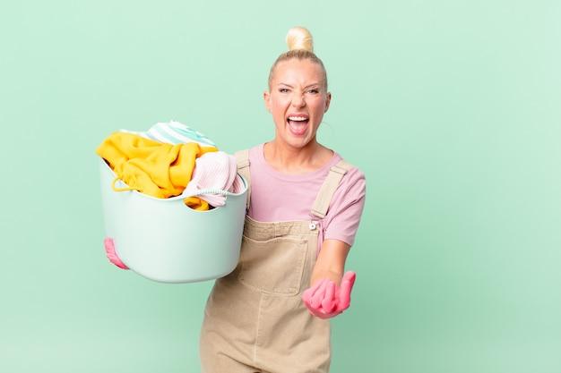 Conceito de mulher loira e bonita parecendo zangada, irritada e frustrada ao lavar roupas