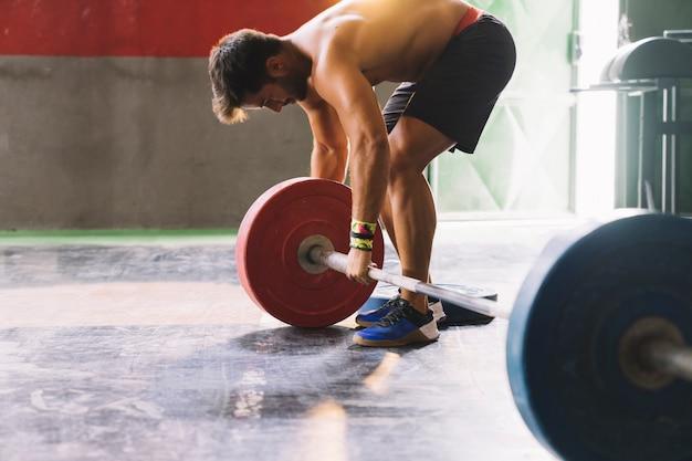 Conceito de musculação com barra de montagem masculina