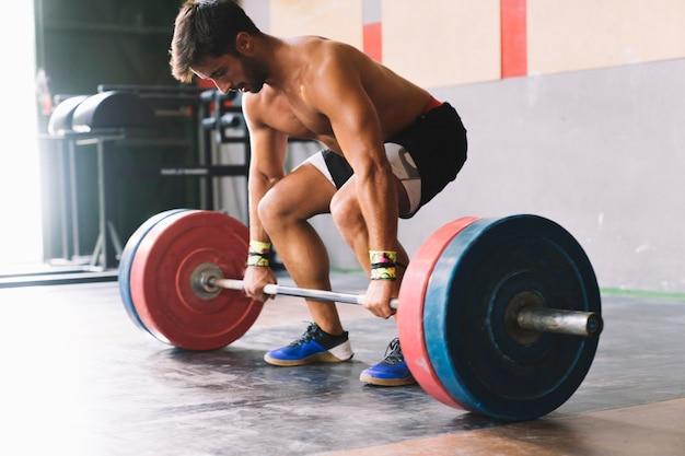 Conceito de musculação com homem forte e barbell