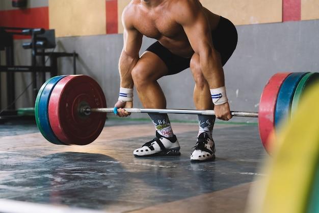 Conceito de musculação com homem forte segurando barbell