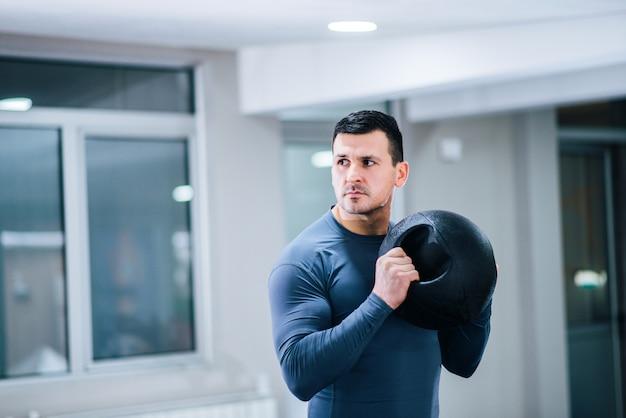 Conceito de musculação. homem musculoso bonito segurando bola de peso.