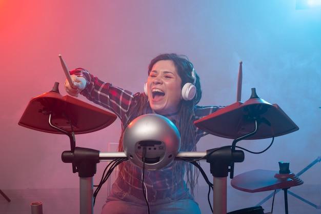 Conceito de música, bateria e hobby - jovem tocando bateria eletrônica no clube