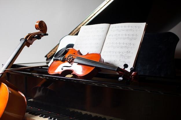 Conceito de música clássica: violoncelo, violino, piano e uma partitura